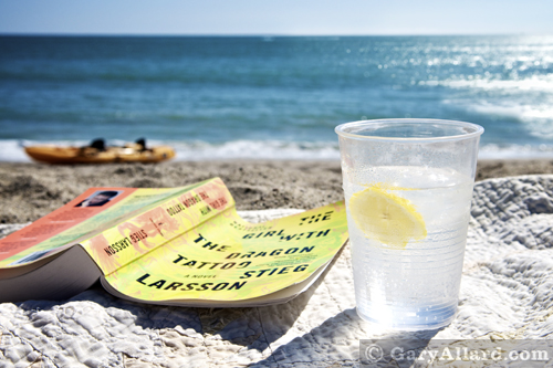 Beach scene with ocean, book and cocktail